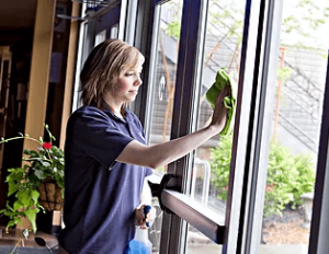 woman cleaning windows at a business wearing a blue work polo and using professional cleaning tools