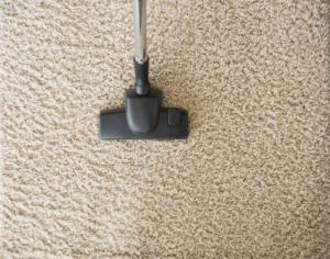 vacuuming tan colored carpet during a deep clean