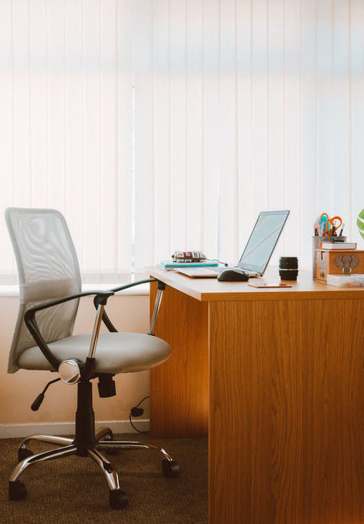 grey office chair sitting at a wooden office desk