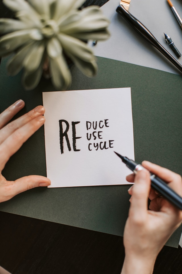 someone writing reduce reuse recycle on a square piece of paper on green background