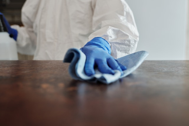 someone cleaning and wood surface with gloves and proper ppe