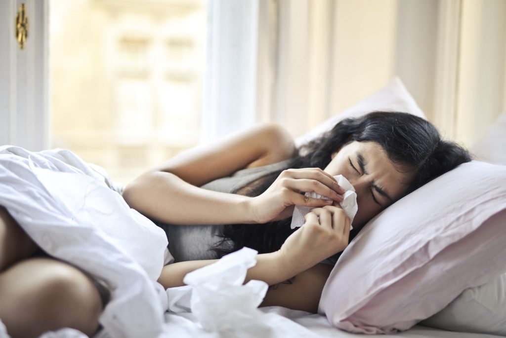 girl laying in bed covered in blankets and using tissues to blow nose